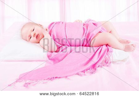 Adorable baby girl lying down in child's bedroom wrapped in beautiful pink blanket, carefree childhood, bedtime concept