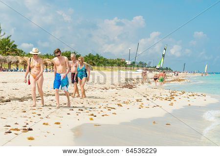 VARADERO,CUBA - APRIL 28,2014 : Tourists walking along the shore on a beautiful sunny day at the beach