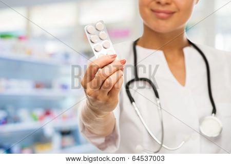 Young positive brunette doctor woman holding pills in drug store