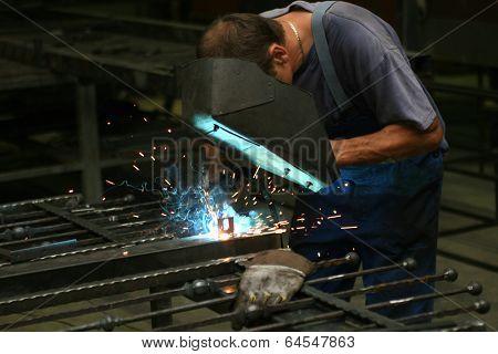 Welder in a workshop making a fence