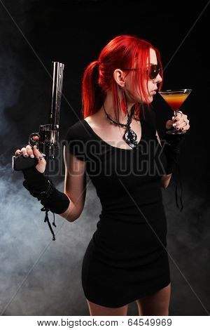 Sexy red hair woman with a gun and a cocktail