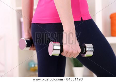 Young beautiful fitness girl exercising  at home, close up