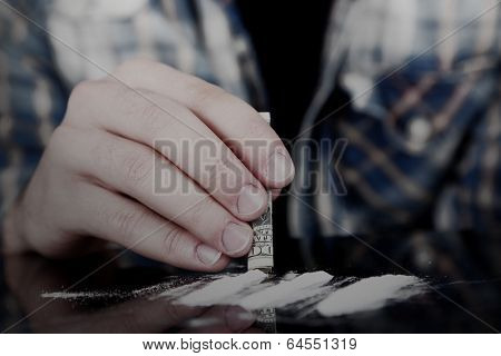 Drug abuse concept - man snorting cocaine