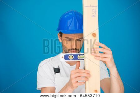 Handsome young workman in a hardhat using a spirit level holding it horizontally against a plank of wood against a blue background