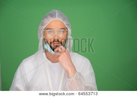 Bearded young male laboratory technician in a sterility suit, goggles and a mask on a green background with copyspace