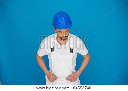 Workman in a blue hardhat with his thumbs hooked in his dungarees standing looking down against a blue background with copyspace