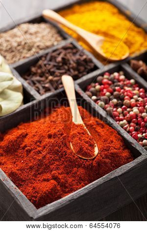 spices in box: pink  black pepper, paprika powder, curry, bay leaf; anise; clove; cumin