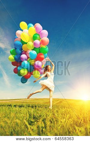 Happy birthday woman against the sky with rainbow-colored air balloons in her hands. sunny and positive energy of nature. Young beautiful girl on the grass in the park.