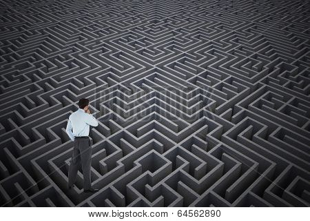 Thoughtful businessman with hand on chin against difficult maze puzzle