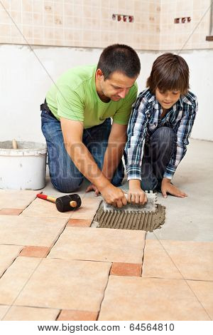 Boy Learning How To Spread Adhesive For Ceramic Floor Tiles