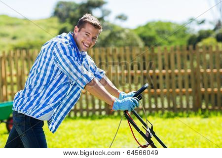 handsome young man pushing lawnmower in home garden
