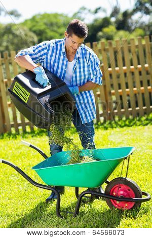 young man emptying lawnmower grass into a wheelbarrow after mowing
