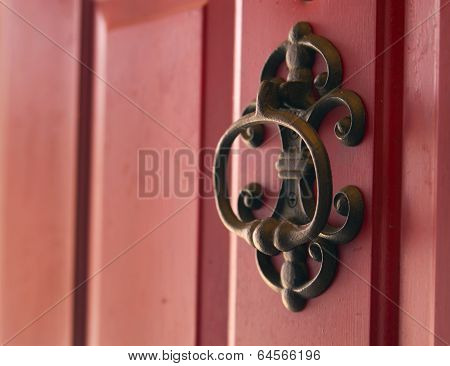 Iron cast door knocker on red door