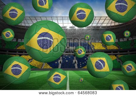 Footballs in brasil flag colours against large football stadium with brasilian fans