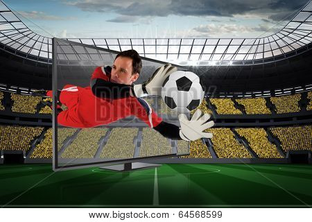 Composite image of fit goal keeper saving goal through tv against vast football stadium with fans in yellow