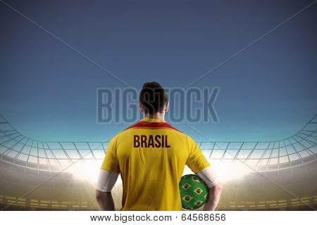 Brasil football player holding ball against large football stadium under blue sky
