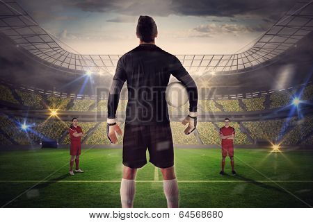 Composite image of goalie facing opposition against large football stadium with lights