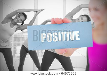 Fit blonde holding card saying positive against fitness class in gym