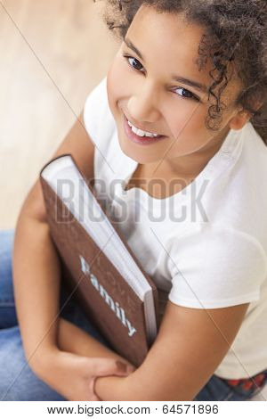 Beautiful happy African American mixed race girl child with family photo album or book