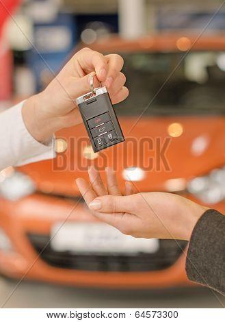 Female Hand Getting Modern Car Key On A Car Background