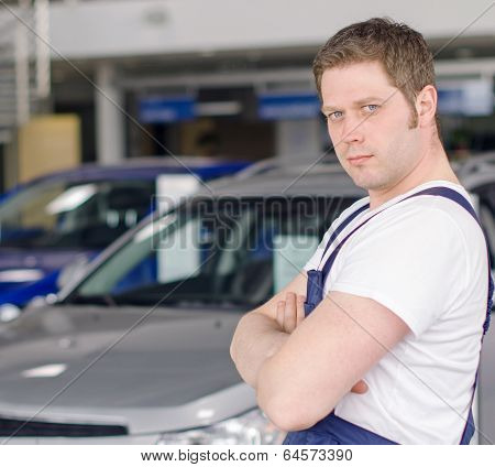 Young Handsome Mechanic In Car Dealership. Place For Text.