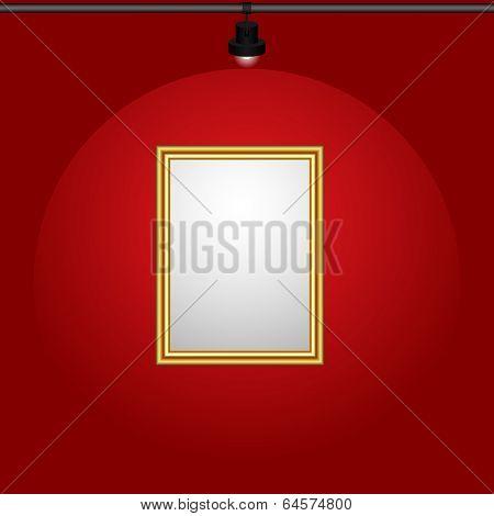 Illuminated gilt-framed blank painting hanging on the crimson wall.