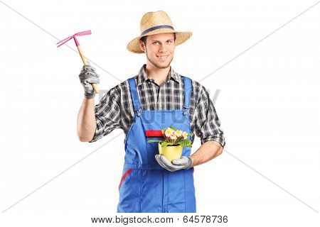 Male gardener holding flower plant and a mattock isolated on white background