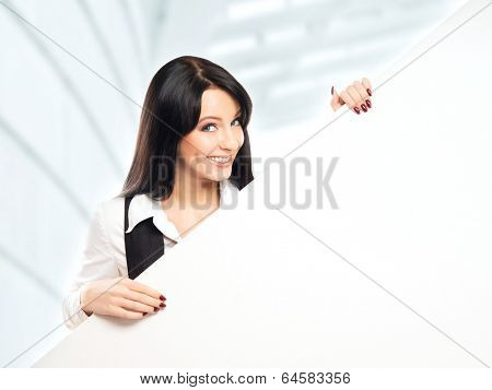 Young, confident, successful and beautiful business woman with a blank billboard over office background