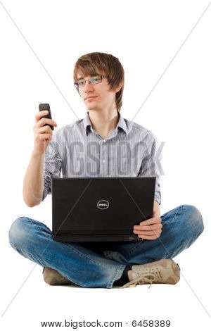 Young Man With Laptop And Writing Sms