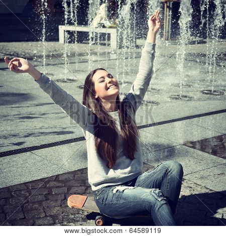 Beautiful excited teen girl pleased youth and sunny spring day sitting on skateboard, urban outdoor near fountain