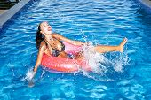 stock photo of flesh air  - Woman floating in an inner tube in a swimming pool and laughing - JPG