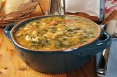 stock photo of kale  - A healthy white bean and kale soup with dinner rolls