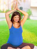 stock photo of pregnancy exercises  - Portrait of beautiful pregnant woman with closed eyes engaged in yoga outdoors - JPG