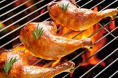 stock photo of thighs  - Grilled chicken thigh on the flaming grill - JPG