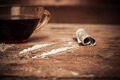 foto of crack cocaine  - A cup of coffee with lines of cocaine and a rolled up banknote next to it - JPG