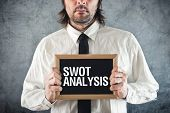 stock photo of swot analysis  - Businessman holding blackboard with SWOT ANALYSIS title - JPG
