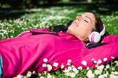 picture of rest-in-peace  - Relaxed female athlete resting and listening music with headphones after workout. Woman lying down on grass and spring flowers. Healthy lifestyle and happiness concept.