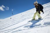 stock photo of snowboarding  - Young girl snowboarder in motion on snowboard in mountains - JPG