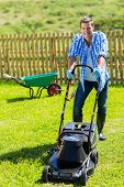 picture of grass-cutter  - cheerful man lawn mowing in his home garden - JPG