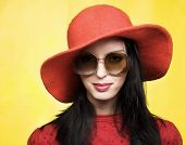 stock photo of panama hat  - Portrait of young woman in sunglasses and red hat in retro style - JPG