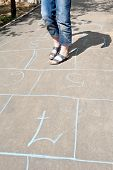 stock photo of hopscotch  - girl playing in hopscotch on urban alley in sunny day - JPG