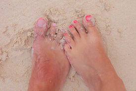 stock photo of wet feet  - bare feet and toes of a young couple in wet sand - JPG