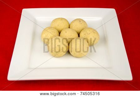 Round Indian Laddu Sweets On A White Square Plate