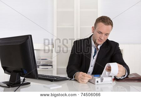 Occupation controller: young businessman looking at paper roll and counting finances.