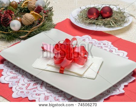 Traditional Christmas Eve white wafer on a plate with red cockade