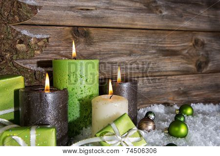 Four burning apple green christmas candles on wooden background.