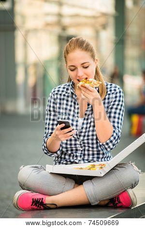 Teenager eating pizza looking in phone