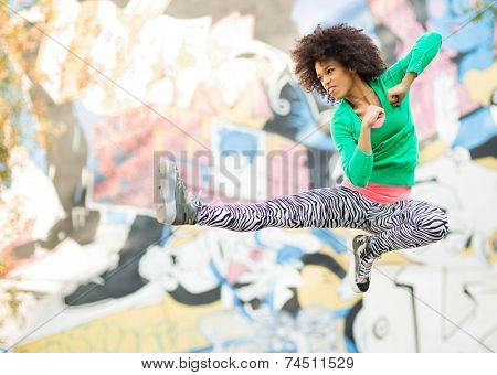 Young woman kicking in mid air