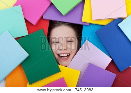 Happy young student covered with books - showing only a smiling face