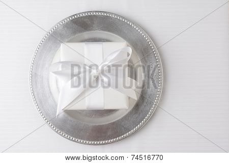 High angle shot of a gift wrapped in white paper and tied with a white ribbon. The present is in the middle of a silver charger on a white tablecloth. Horizontal format with copy space.